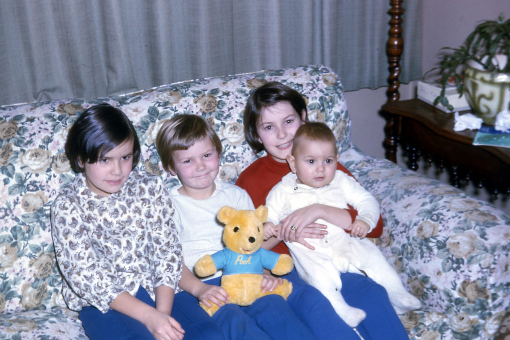 three girls and a baby boy on a couch