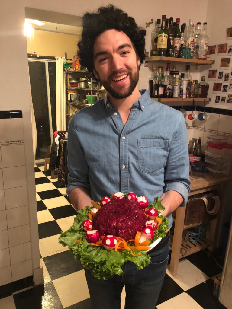 man with curly hair holding jellied salad