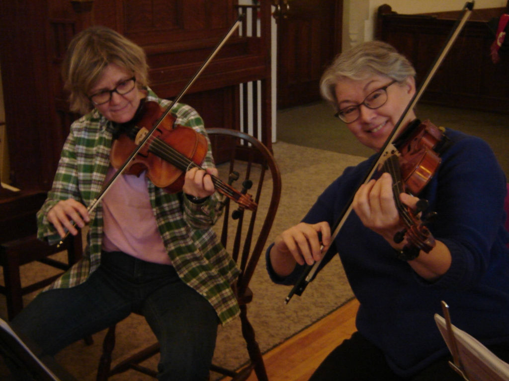two smiling women playing the fiddle